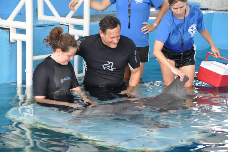 Isabella and Craig  getting acquainted with Winter,  Abby has her hand on Winter's dorsal fin.